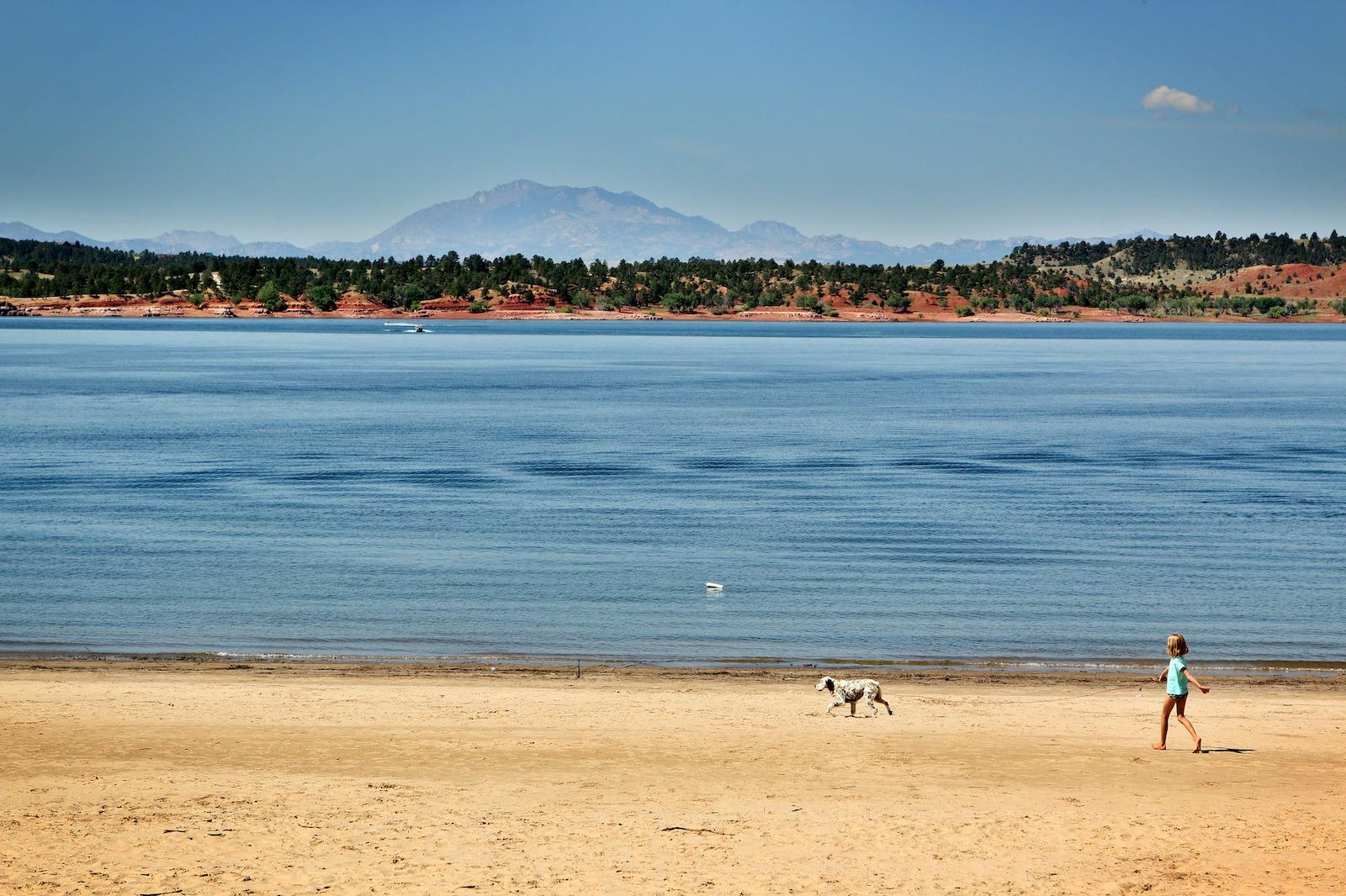 Child and dog walking on the shore of Glendo State Park in Platte County, Wyoming