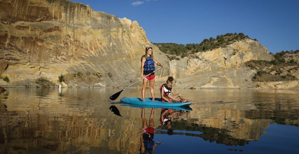 Two people paddle boarding in Dinosaurland, Utah.