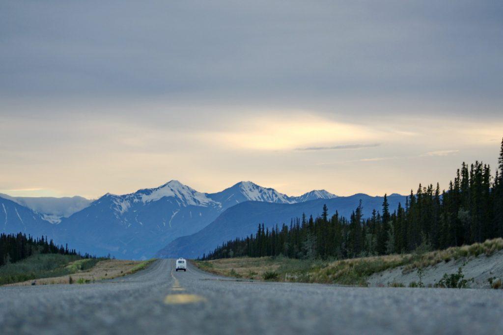 A van driving down a highway in Alaska.