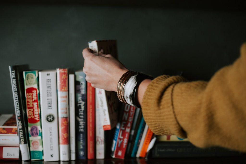 Someone grabbing a book from a shelf.